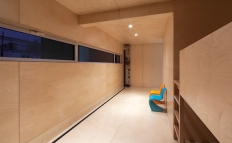 Natural plywood covers the children's room, including the built-in bunk beds, cupboards and closet.
